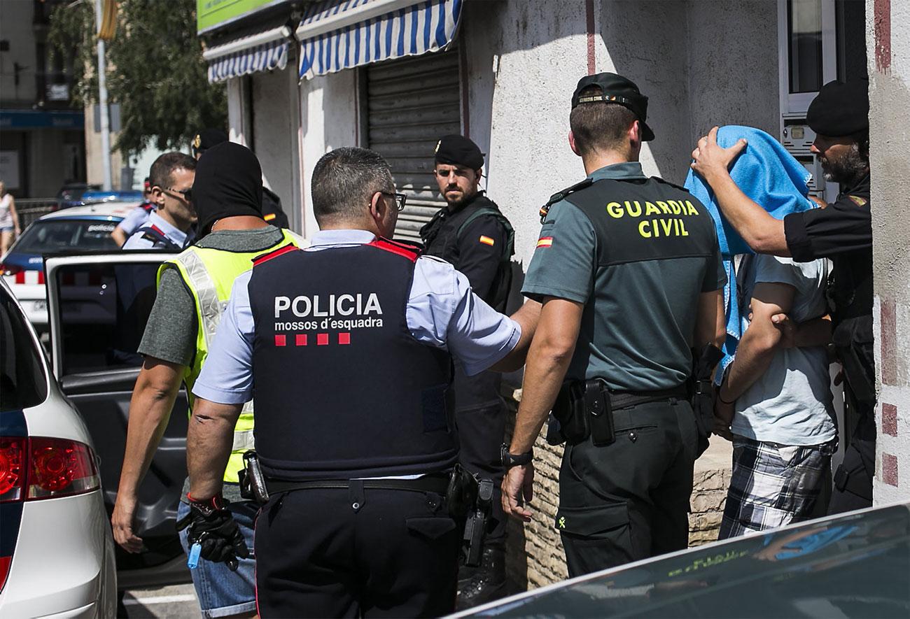 Efectius dels Mossos d'Esquadra i de la Guàrdia Civil efectuant ahir una detenció a Ripoll d'un dels dotze presumptes terroristes implicats en els atemptats